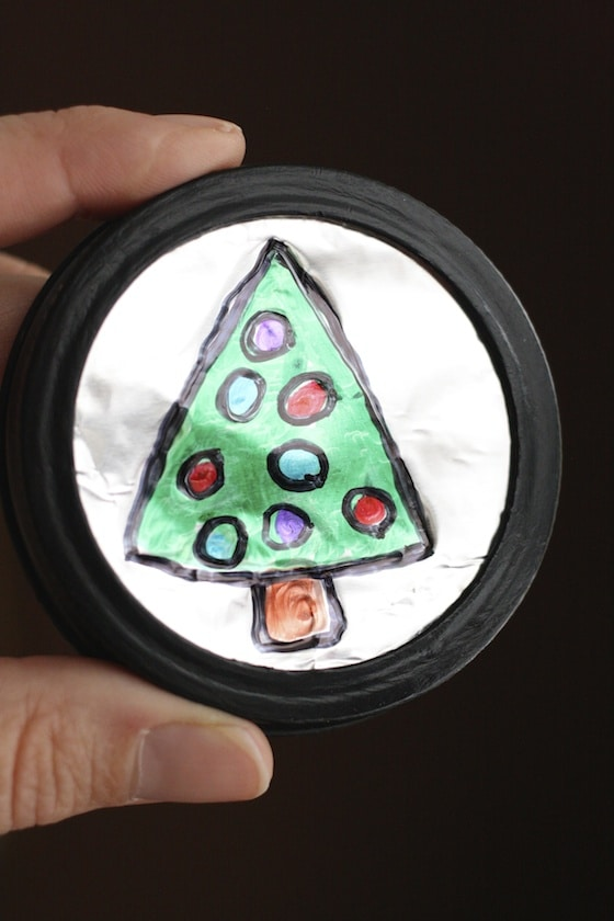 christmas tree drawings on tin foil with Sharpies, in black mason jar lid