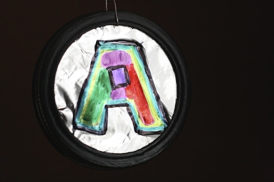 Letter A ornament with foil and sharpies and mason jar lid made by child