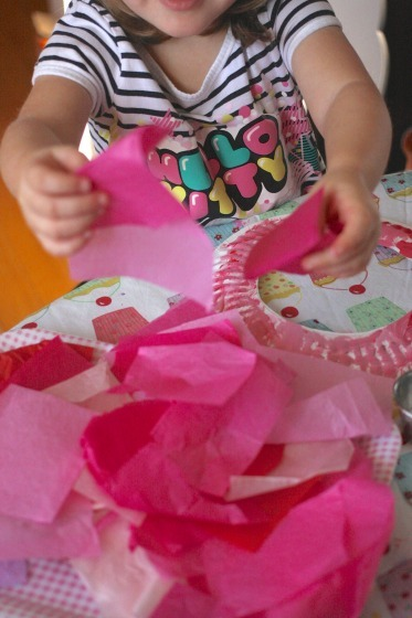 Toddler making tissue paper wreath