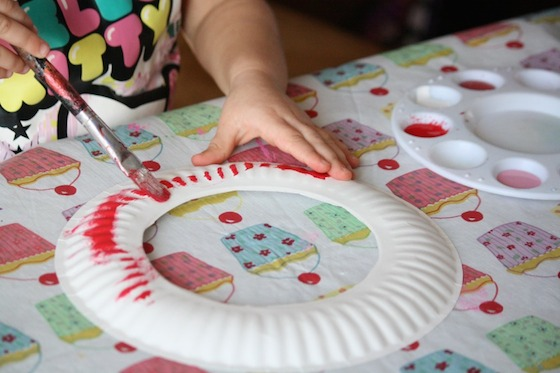 Toddler painting paper plate red