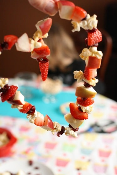 heart shaped bird feeder with fruit and popcorn