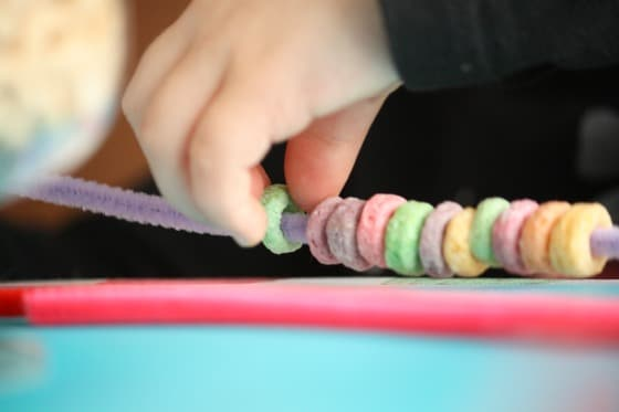 threading fruit loops onto pipe cleaners for the birds