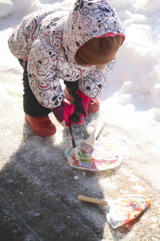 toddler painting coffee filters with snow