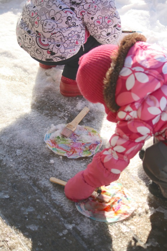 toddlers painting with snow on coffee filters