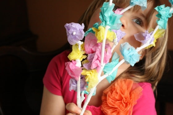 Child holding tissue paper blossom tree craft