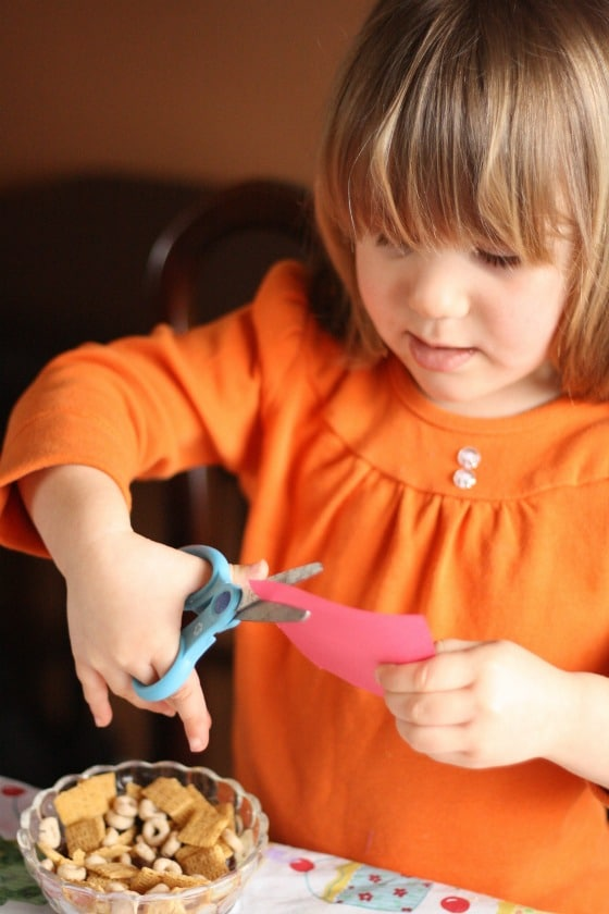 Preschooler cutting paper flowers out of card stock