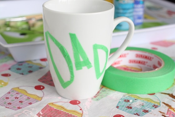 Dad spelled in painters tape on a white mug