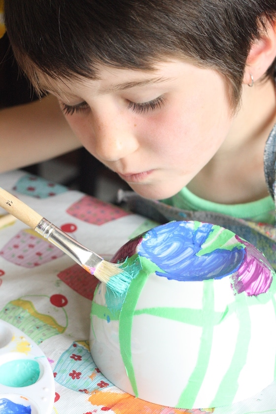 child painting bowl with tape resist technique