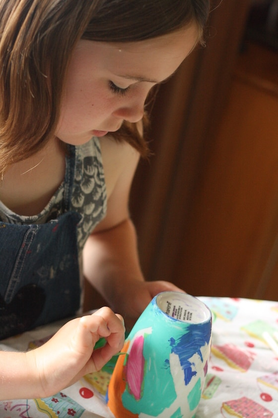 child removing painters tape from painted mug