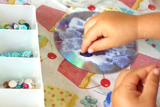 child gluing craft gems to cd