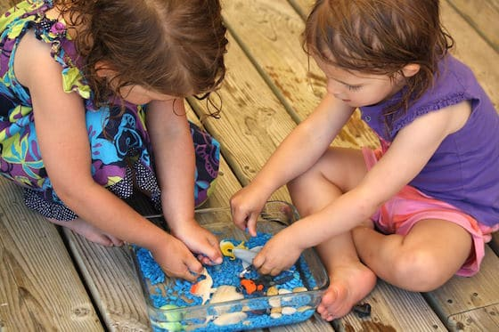 toddler and preschooler playing with small ocean sensory bin