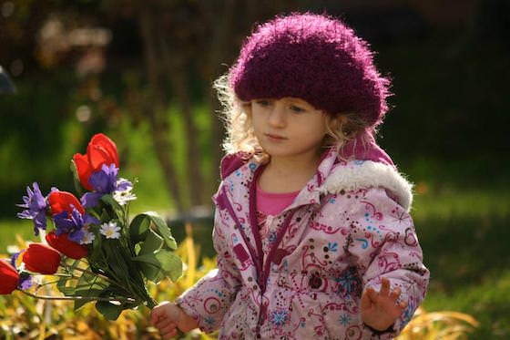 preschooler carrying flowers in sunshine