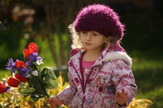 preschooler carrying flowers in sunshine