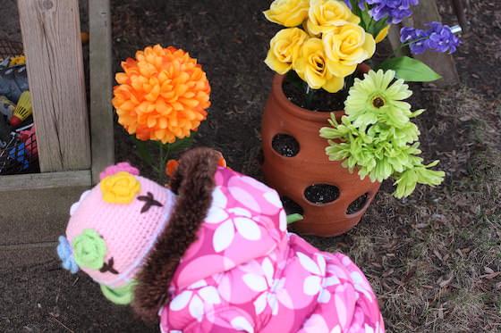 planting dollar store flowers beside sandbox