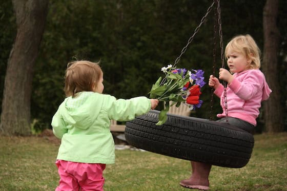 baby giving flowers to toddler on the tireswing