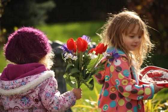 preschoolers holding pretend parade holding flowers