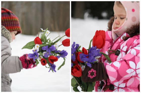 Playing with artificial flowers in the yard in winter