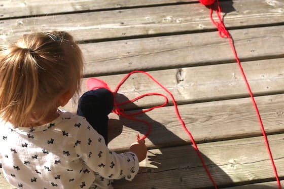Toddler playing with yarn