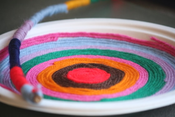 paper plate and twig wrapped with yarn