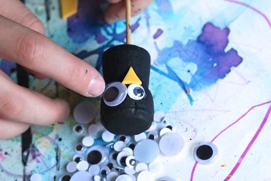 gluing googly eyes on cork craft