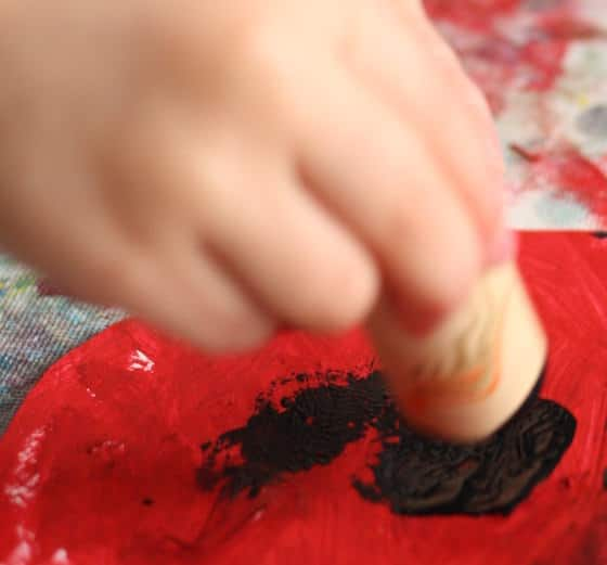 preschooler stamping black paint on red paper plate poppy