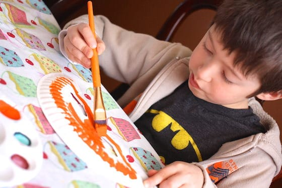Boy painting a paper plate mask