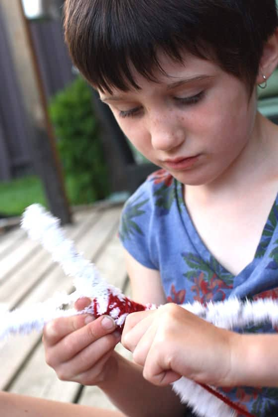 child wrapping twigs with yarn