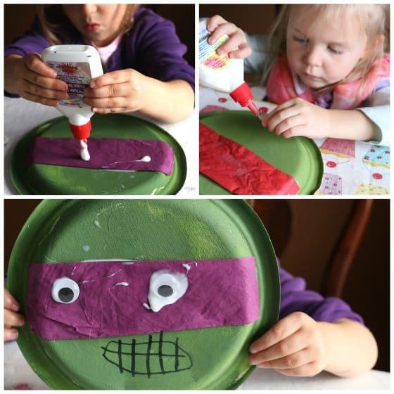 Gluing googly eyes on Teenage Ninja turtle craft