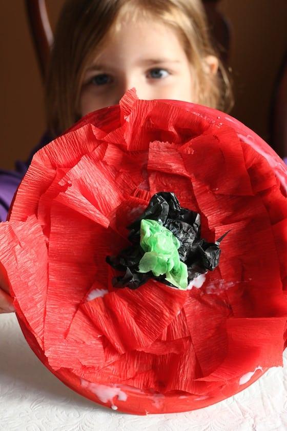 preschooler holding crepe paper poppy craft