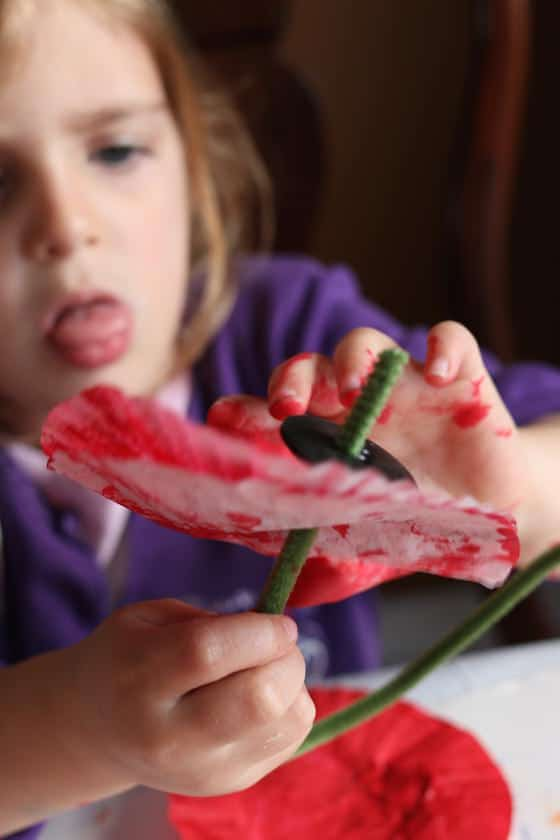 preschooler putting pipe cleaner stem and black button on poppy craft