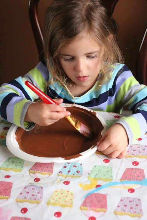 Child painting paper plate brown