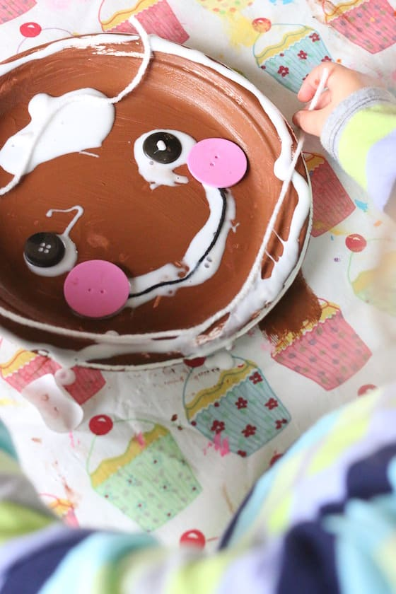 preschooler decorating a gingerbread man paper plate