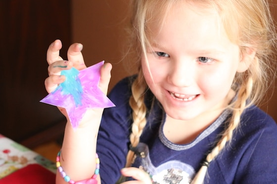 child holding up star coloured with sharpies