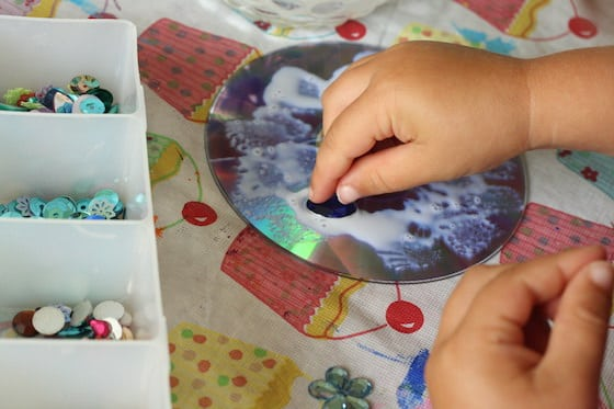 Child gluing gems to a cd