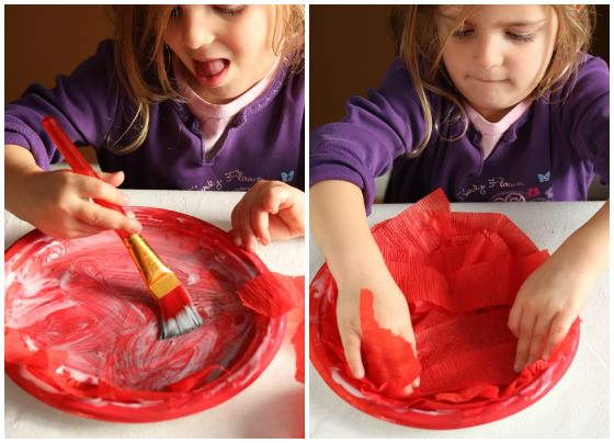 child gluing red crepe paper to painted paper plate