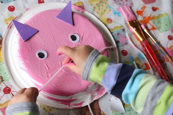 Child gluing whiskers on cat craft