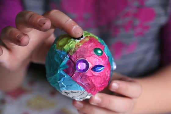child gluing gems on tinfoil ornament