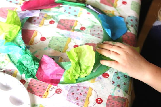 preschooler gluing tissue paper to paper plate