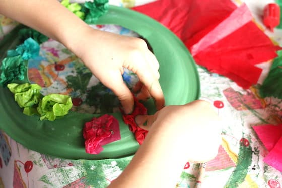 child gluing tissue paper to painted paper plate