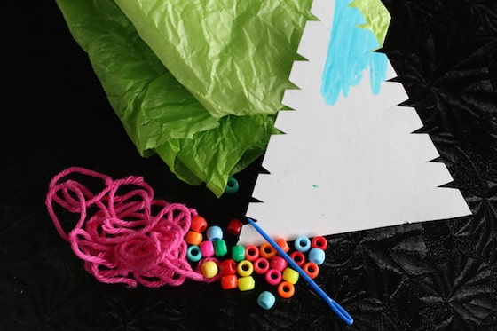 beads, yarn, sewing needle, tissue paper, cardboard