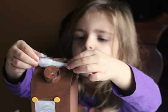 child gluing cotton balls on non-edible gingerbread house craft
