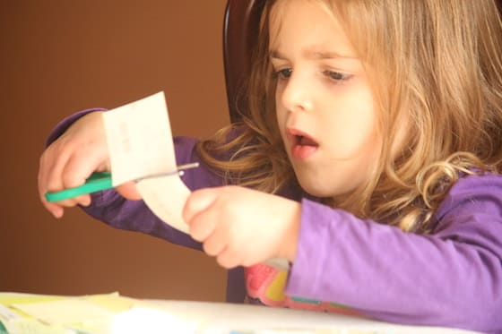 child cutting paint chip sample