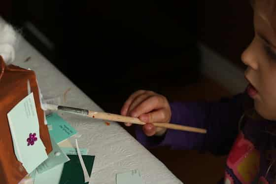 gluing decorations on preschool gingerbread craft