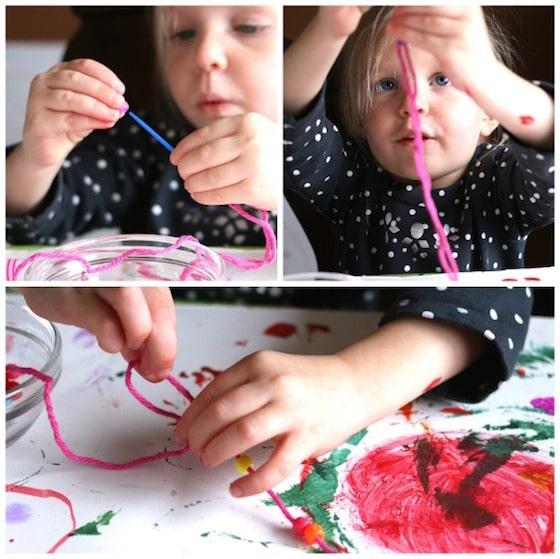 toddler stringing beads onto pink yarn