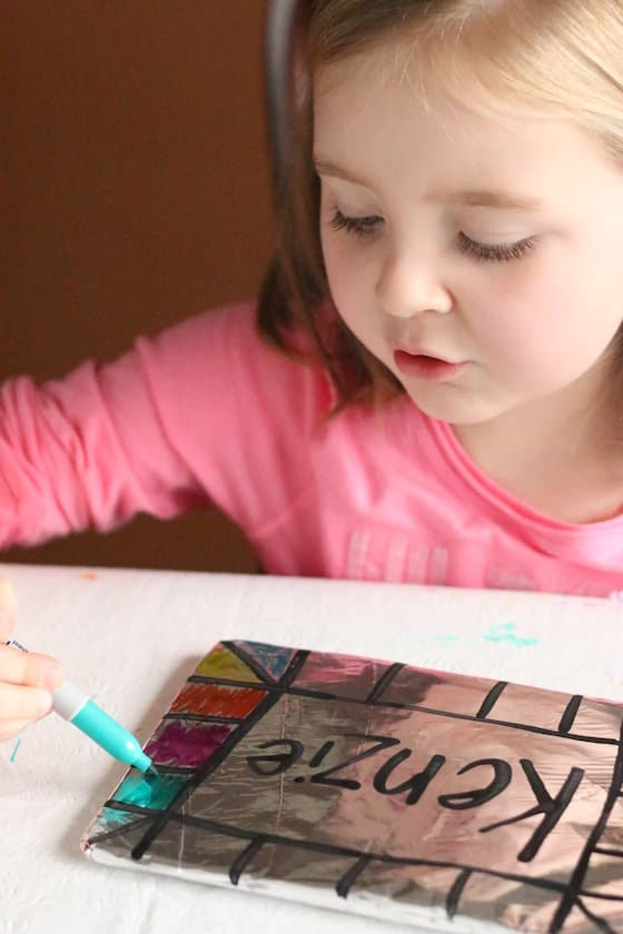 Child colouring her name on tinfoil with sharpie markers