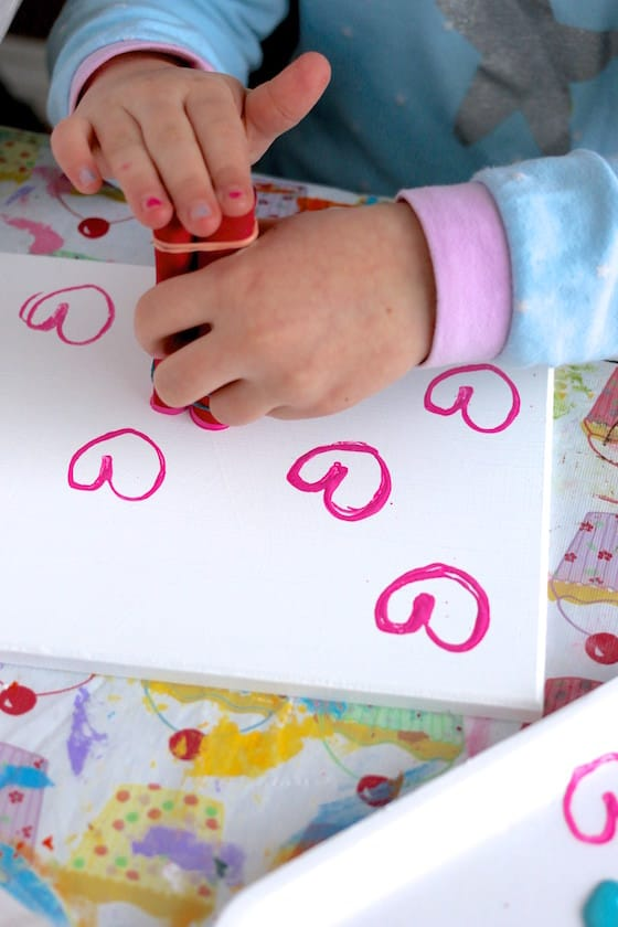 child stamping valentines hearts with toilet paper tube