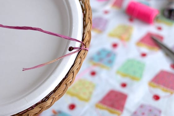 making a bird feeder with a paper plate, wicker paper plate holder and raffia