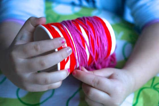 Child wrapping red and pink yarn around a cup