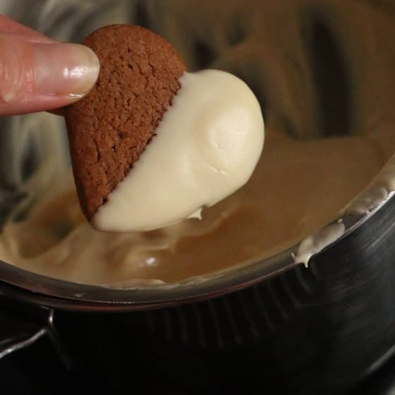 Dipping heart shaped gingerbread cookies in white chocolate