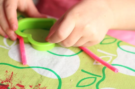 child wrapping pipe cleaner around heart shaped cookie cutter